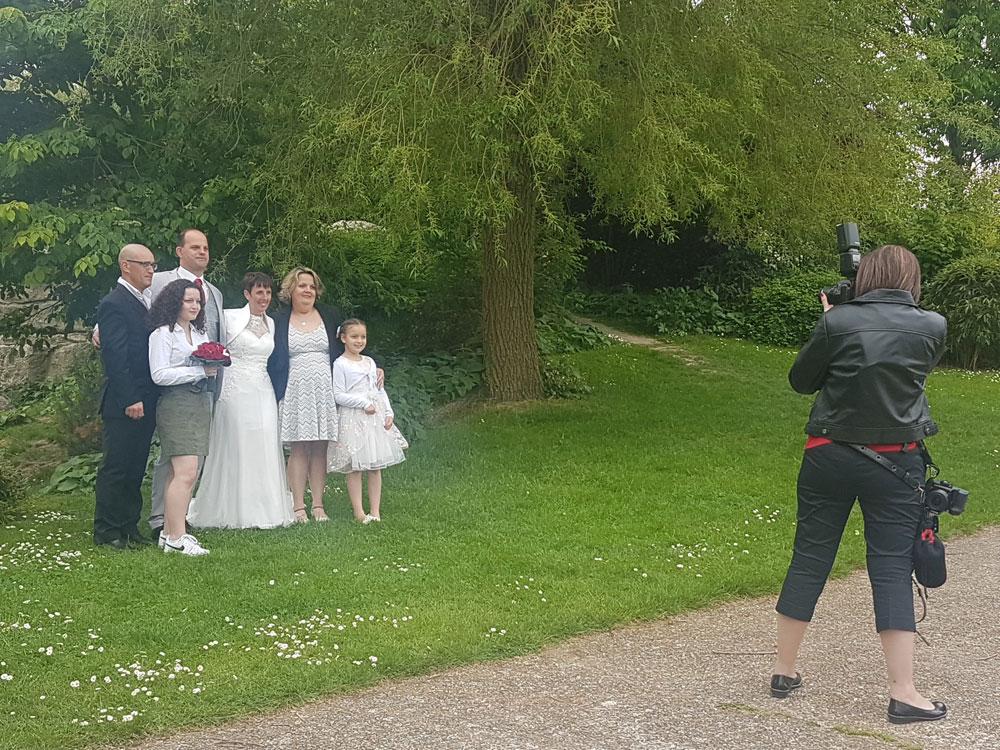 la photographe de mariage au travail pendant la prise de vue de groupe