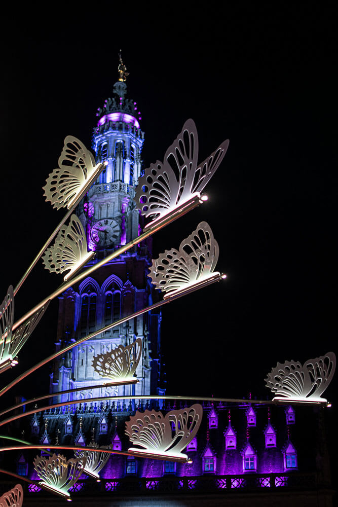 le beffroi d'Arras et un gros plan des décorations de la place des héros