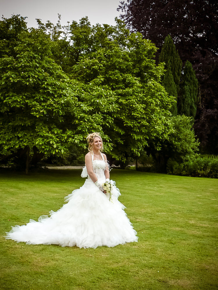 la mariée pose dans le jardin du château